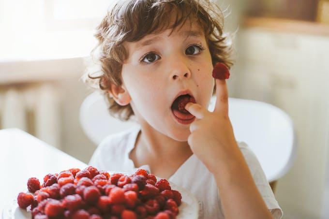 Garçon qui mange des framboises