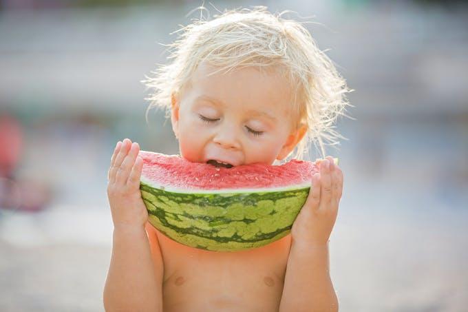 Petit garçon qui mange une pastèque