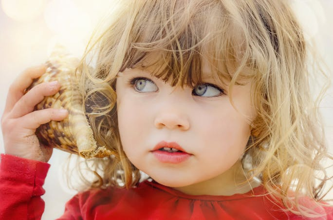 Petite fille qui écoute un coquillage