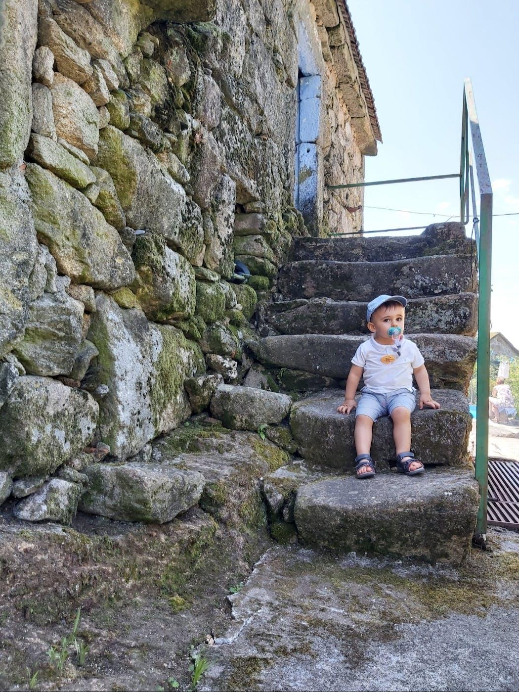 bébé au pied d'un escalier en pierre