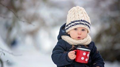 Enfant dans la neige avec une tasse de thé à la main