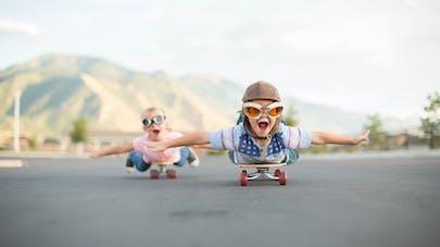 petite fille déguisée en pilote roule, allongée sur son skateboard en faisant l'avion