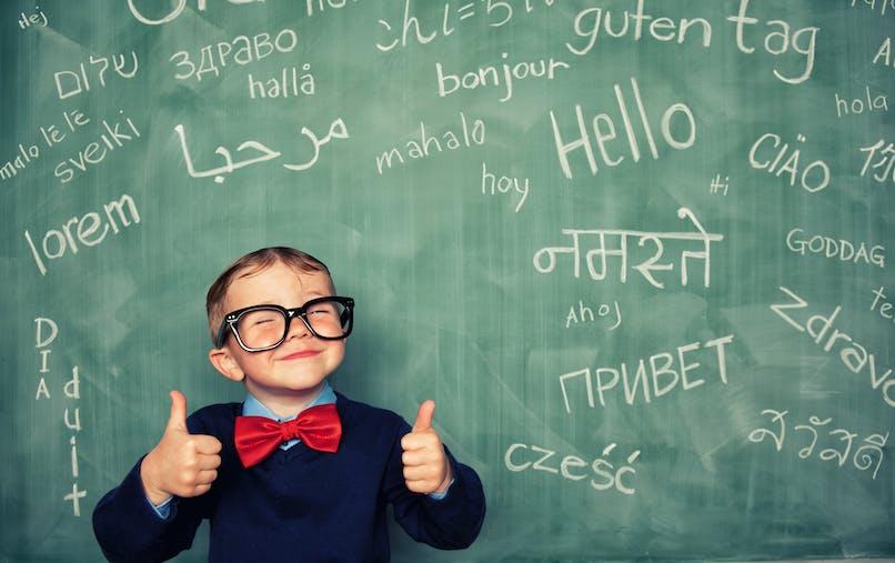Enfant pouces levés avant tableau écrit Hello dans toutes les langues