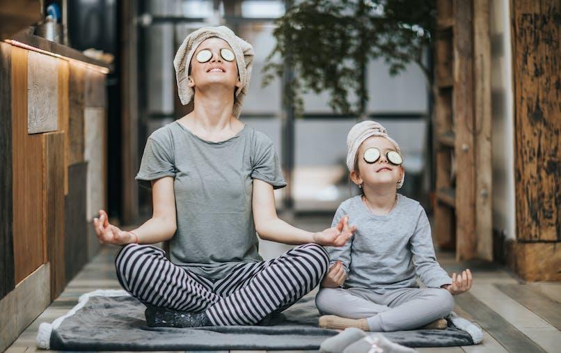 mère et fille assises méditent ensemble