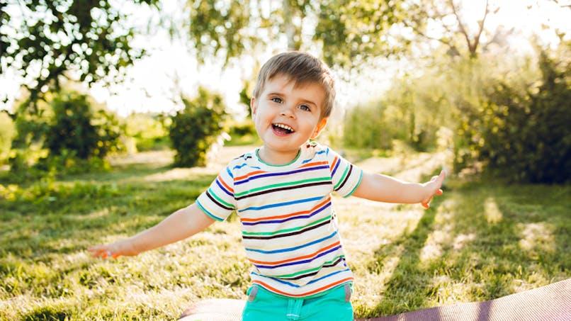 bébé écarte les bras dans le jardin