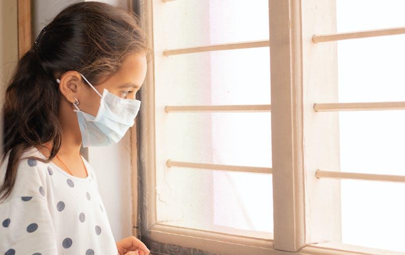 Une jeune fille avec un masque regarde par la fenêtre