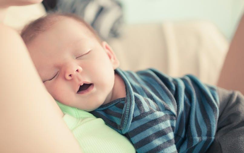 Un bébé dort sur sa maman