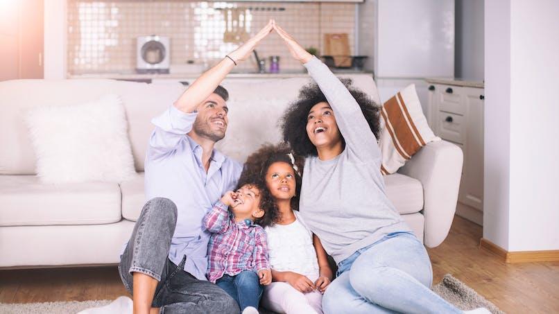 Une famille fait un toit avec ses bras au-dessus de ses enfants