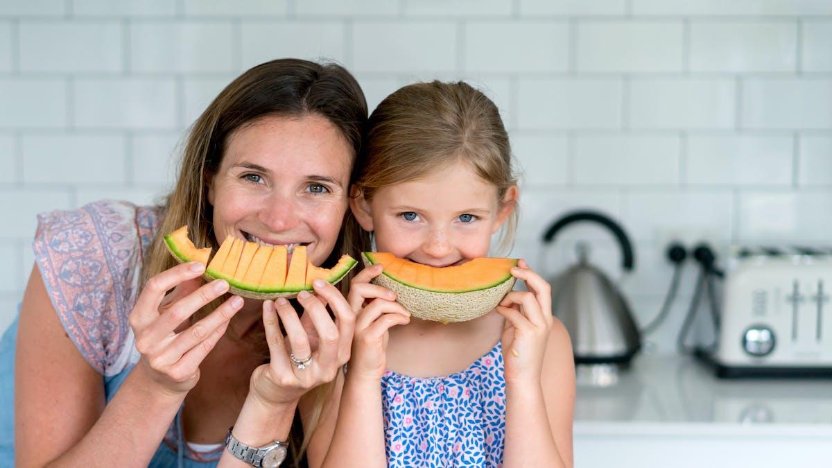 Mère et fille mangeant un melon