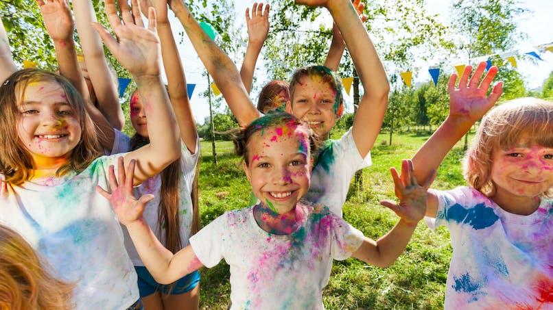 Des enfants jouent avec de la peinture sur corps pendant un festival en plein-air