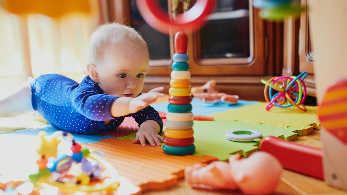 Un bébé curieux semble très attiré par ses jouets de construction