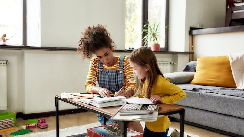 Une jeune femme aide une enfant à faire ses devoirs