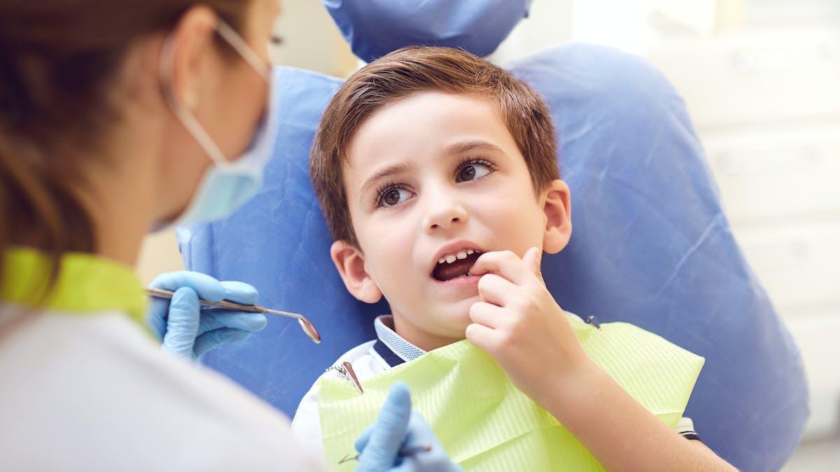 enfant montrant ses dents au dentiste