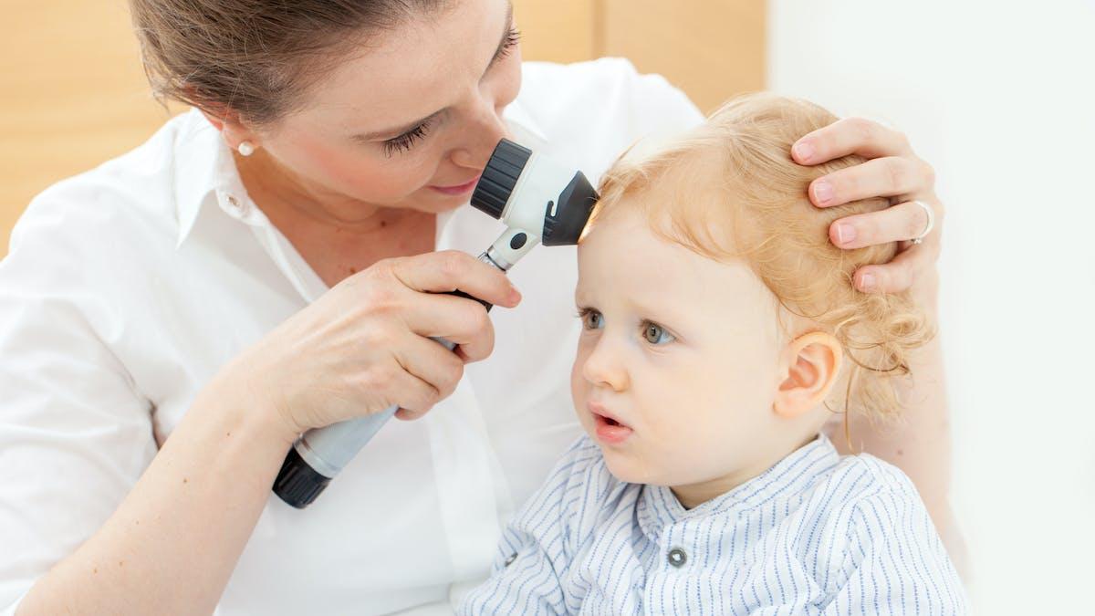 médecin ausculte un grain de brauté sur la tête de bébé