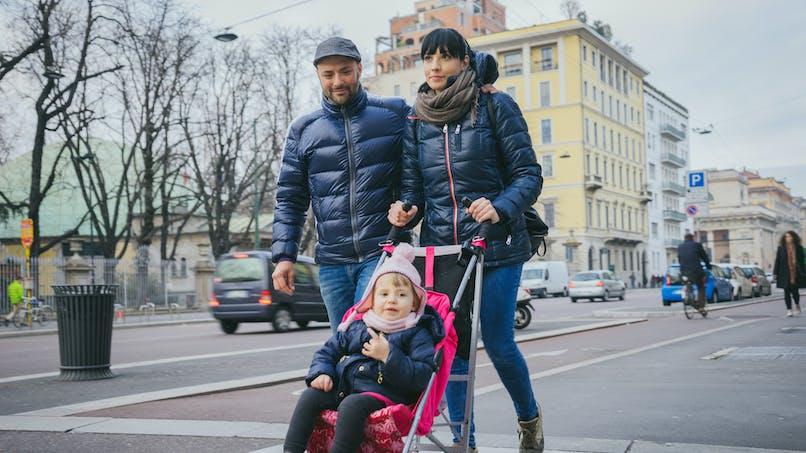 Couple avec enfant dans la poussette dans la rue