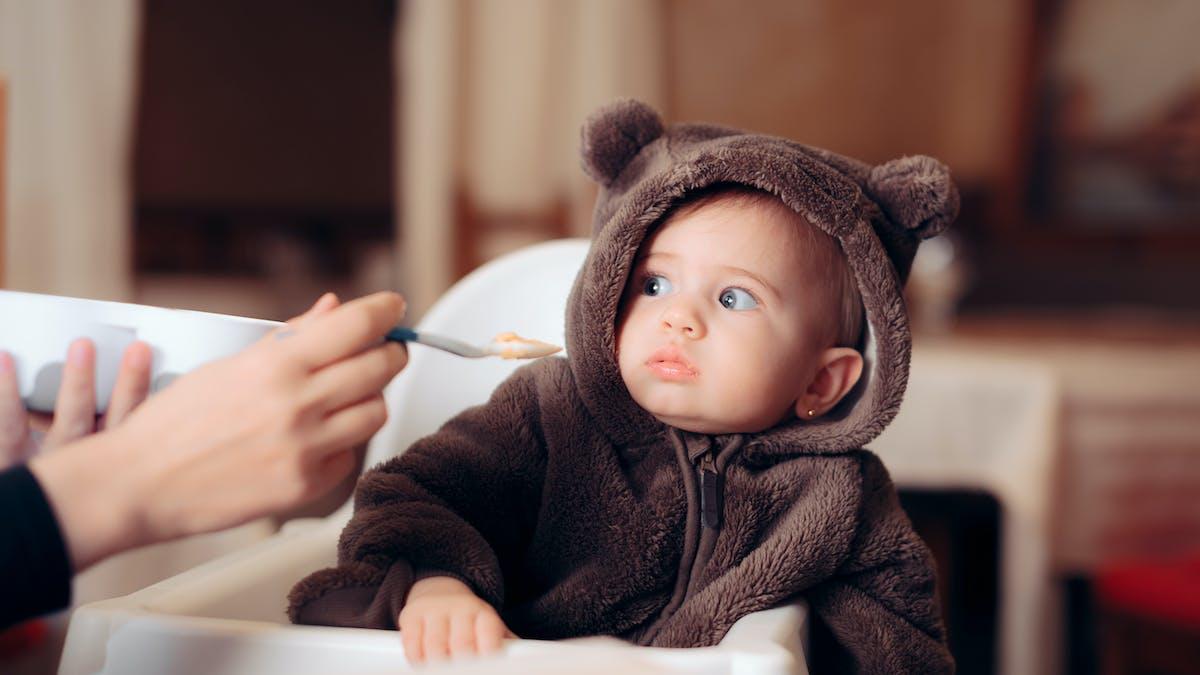 Diversification alimentaire : un bébé de 5 mois hésite face à une cuillère de compote