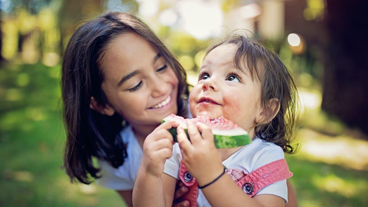 Alimentation bébé mois par mois : un enfant de 12 mois mange une pastèque avec sa grande soeur
