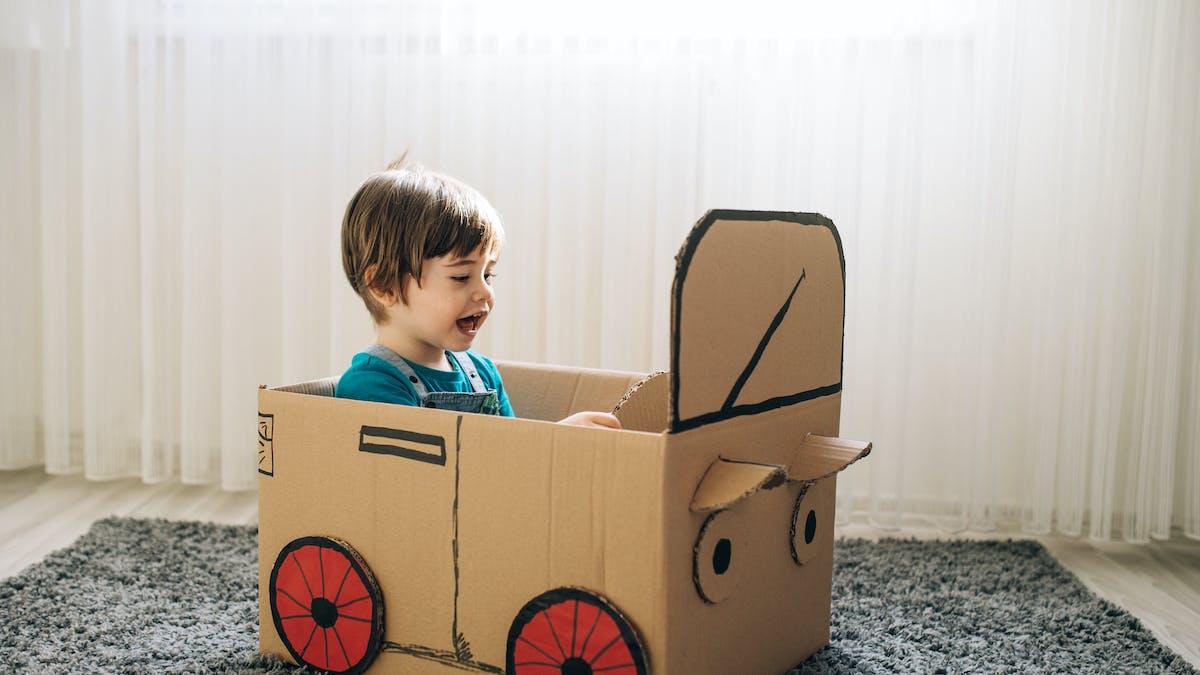 Jeu de petit garçon dans la voiture en carton
