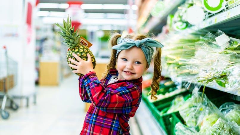 fillette dans un magasin qui tient un ananas