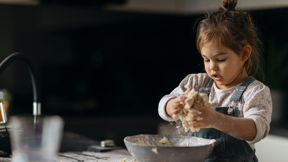 Gluten : une petite fille cuisine une pâte à tarte